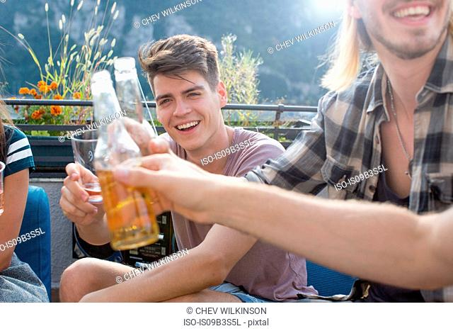 Adult friends raising a toast at roof terrace party
