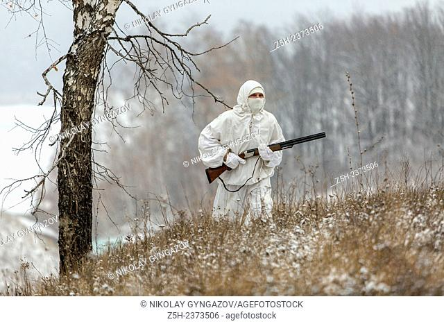 Winter hunting in white camouflage suit. Belgorod region