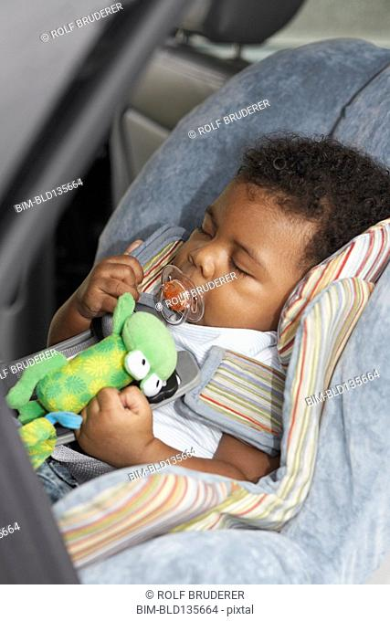 Black baby sleeping in car seat