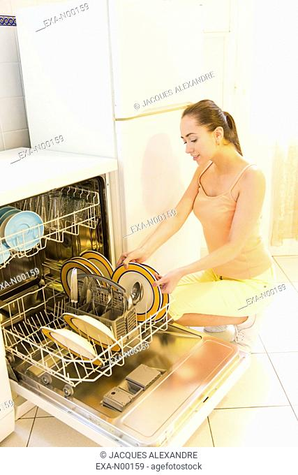 Woman loads dishes into the dishwasher