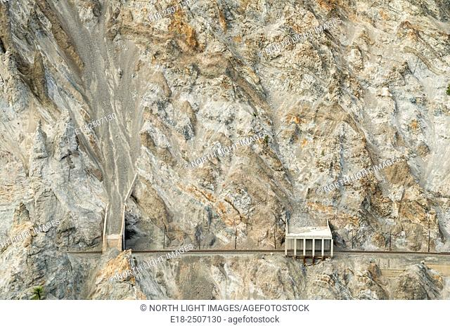Canada, BC, Lytton. Rail line runs below rocky cliff on the edge of the Thompson River Canyon. Concrete sheds built over tracks to divert rockfalls