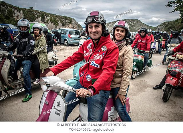 A couple, poses for photographer with his scooter and custom style dressed in Cuevas del Mar beach during Llanes scooters concentration. Asturias