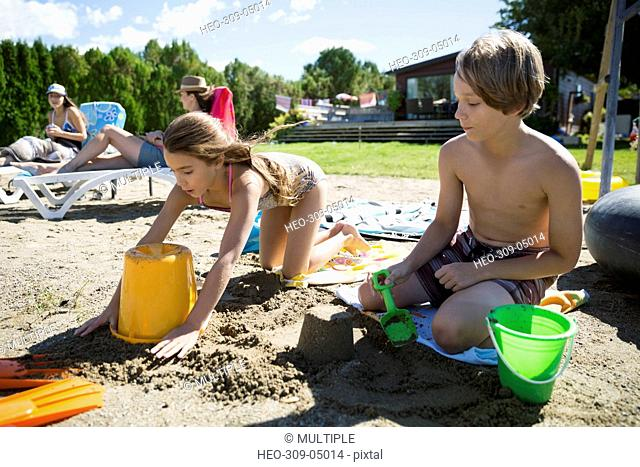 Brother and sister building sandcastle on sunny summer beach