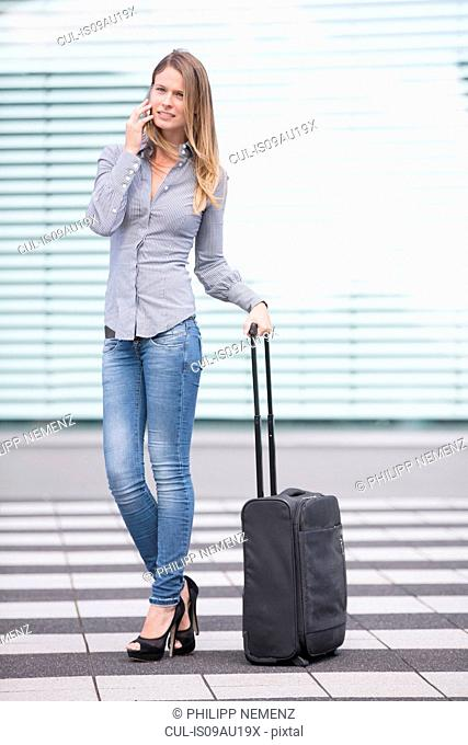 Young businesswoman with wheeled suitcase chatting on smartphone at airport