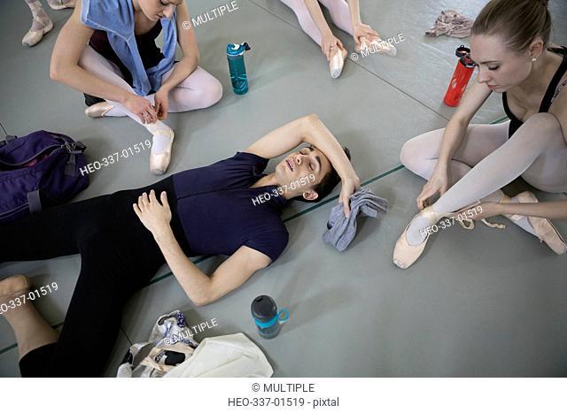 Tired male ballet dancer resting on floor in dance studio