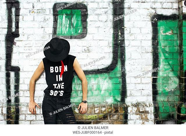 Young man covering his face with a hat wearing t-shirt with saying 'Born in the 90s'