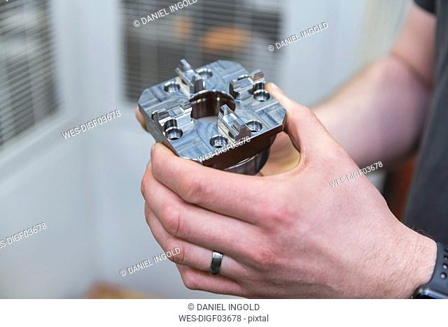 Close-up of man holding workpiece in factory