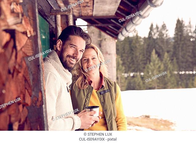Portrait of couple standing outside log cabin in winter, Elmau, Bavaria, Germany