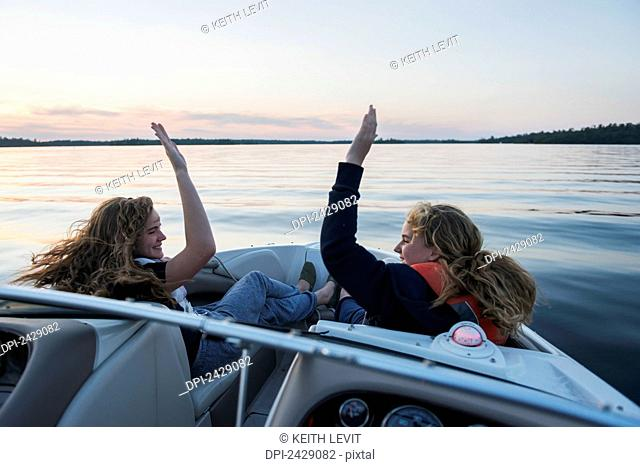 Two teenage girls riding in the front of a boat on a tranquil lake at sunset giving each other a high five; Ontario, Canada