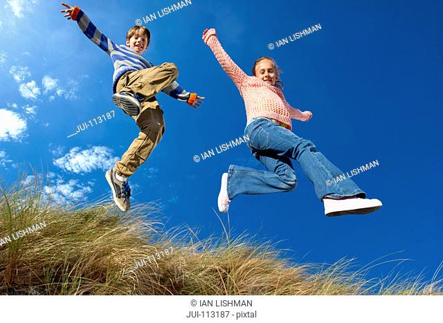 Exuberant brother and sister jumping for joy over grass