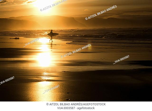 Sunset surfer in Atxabiribil beach, Sopelana, Basque country. The Basque country is a perfect place for surfing with a lot of sand breaks