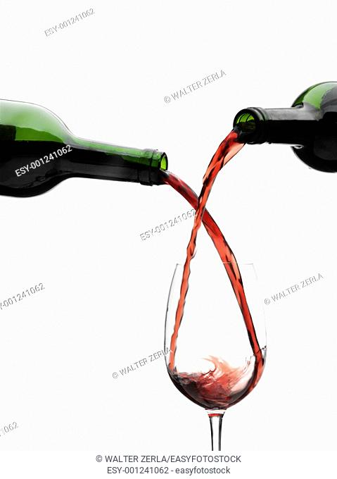 Red wine pouring down from a wine bottles