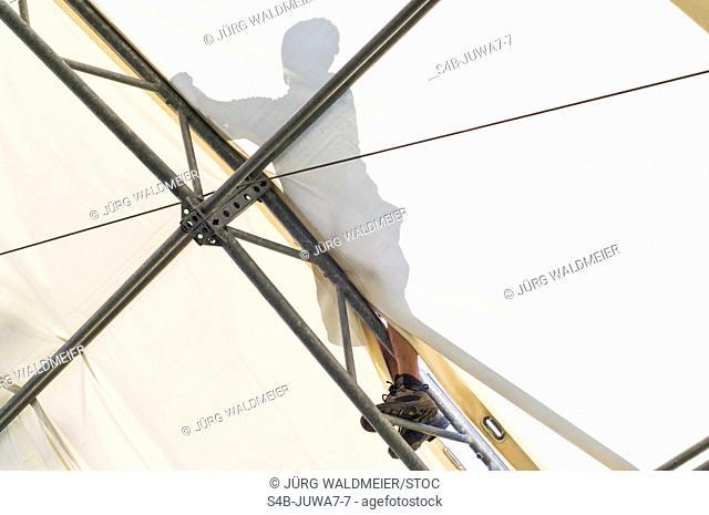 Man mounting on scaffolding