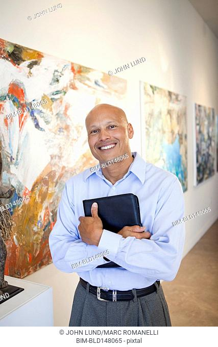 Mixed race art gallery owner standing with paintings