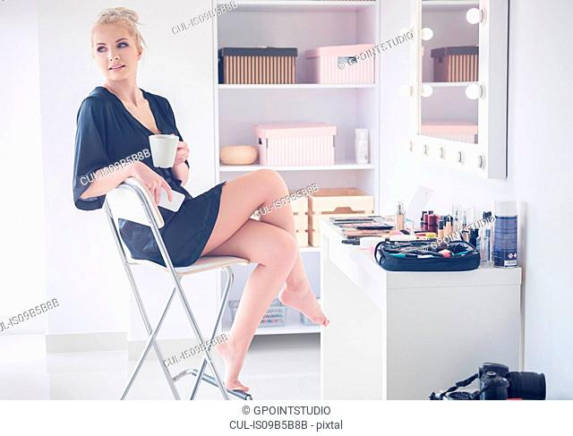 Young female model sitting on stool before photo shoot