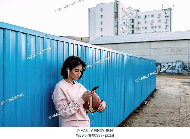 Young woman with basketball, smartphone and earphones at container