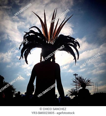 The silhouette of a danzante wearing a plume of feathers during the anual pilgrimage to Our Lady of Guadalupe Basilica in Mexico City, Mexico