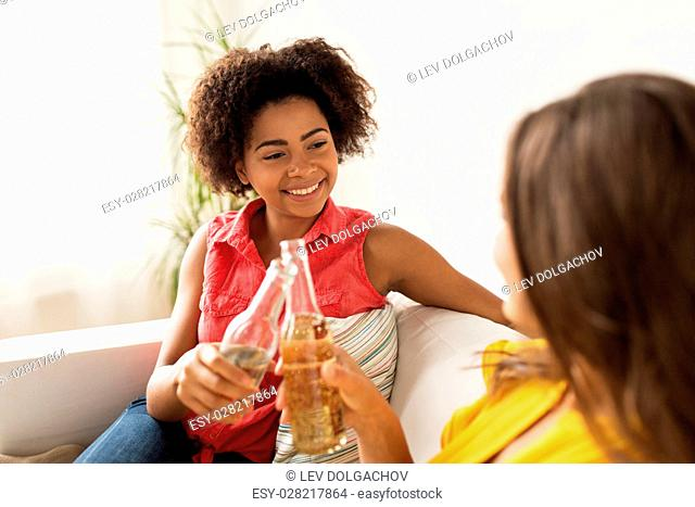 friendship, people, holidays and celebration concept - happy women clinking bottles of beer at home