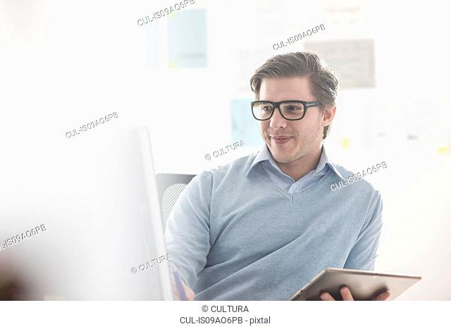 Young businessman using computer and digital tablet at office desk