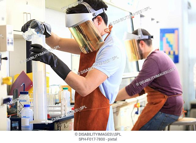 Engineering students wearing protective equipment while working with chemicals in a laboratory