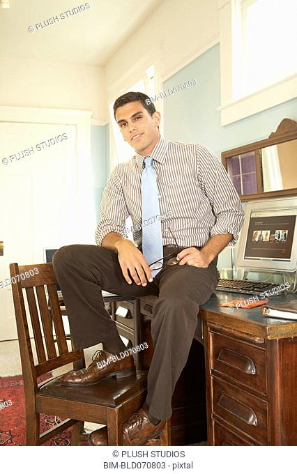 Hispanic businessman sitting on desk