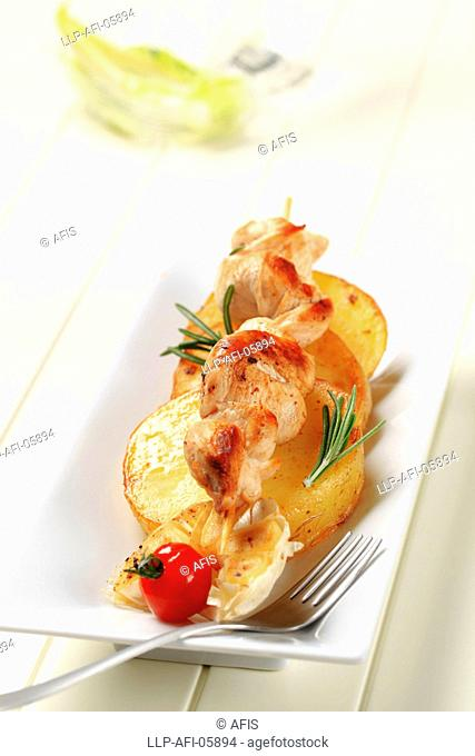 Chicken kebab with slices of pan roasted potato