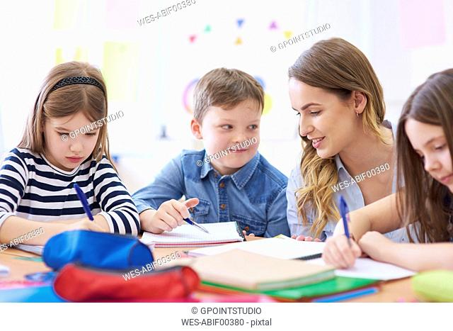 Teacher helping pupils with their tasks in class
