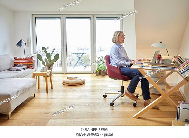 Mature woman at home using laptop at desk