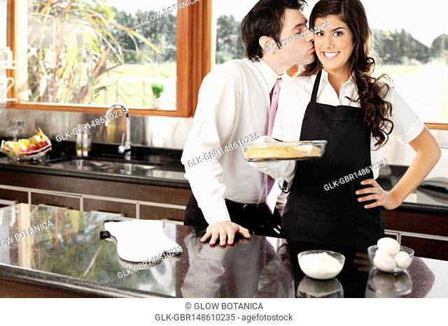 Woman preparing cake with her husband kissing her