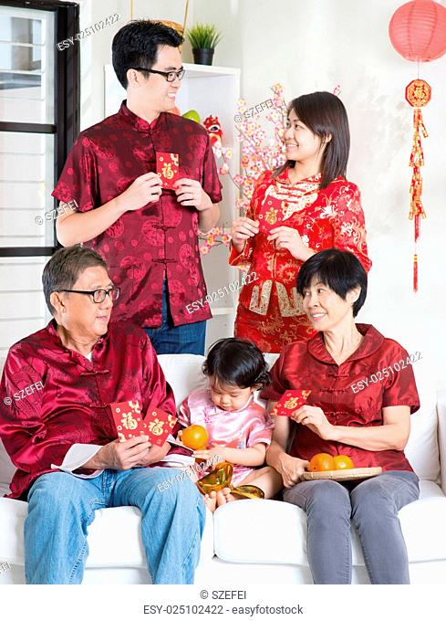 Chinese new year celebration. Happy Asian multi generations family in red cheongsam showing red packets while reunion at home