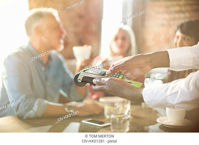 Waiter using credit card reader at restaurant table