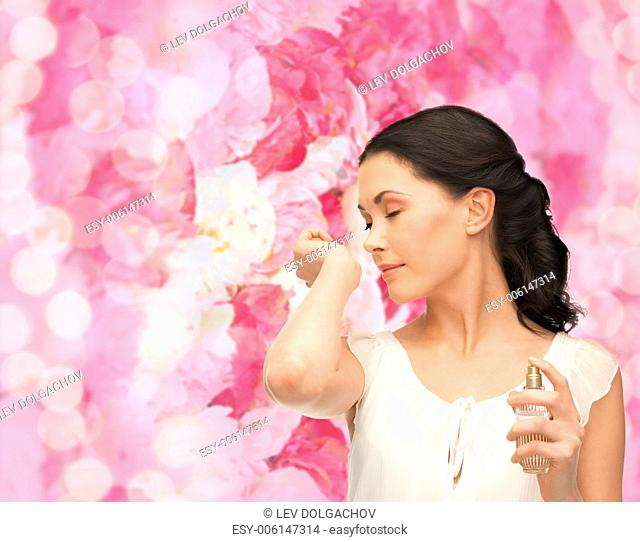 picture of beautiful woman smelling pefrume on her hand