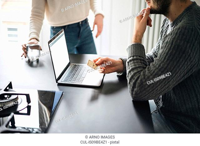 Couple with credit card using laptop, cropped