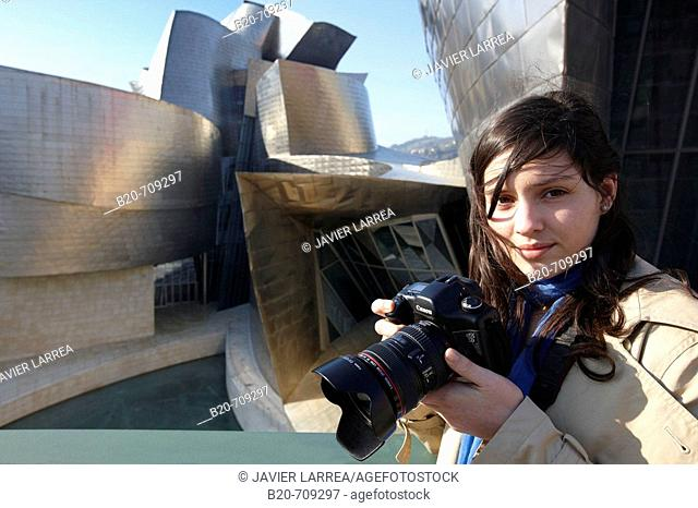 Young woman with camera in front of the Guggenheim Museum, Bilbao. Biscay, Euskadi, Spain
