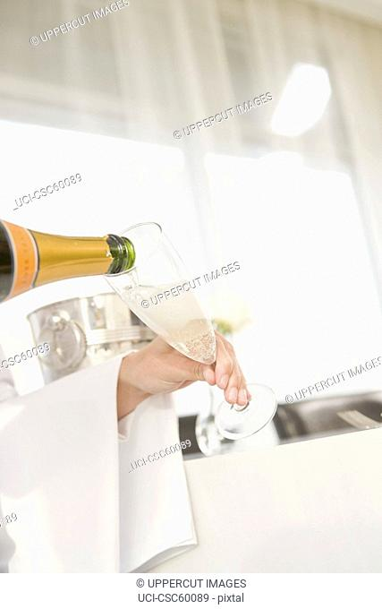 Waitress pouring champagne