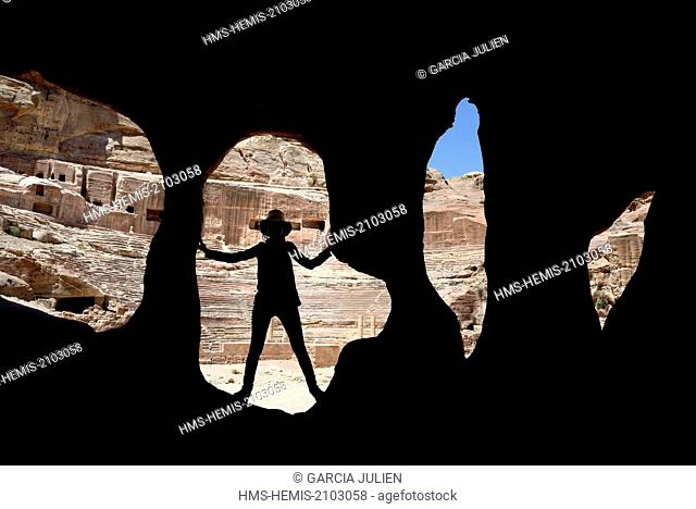 Jordan, Nabataean archeological site of Petra, listed as World Heritage by UNESCO, silhouette of a woman at the entrance of a cave near the theatre