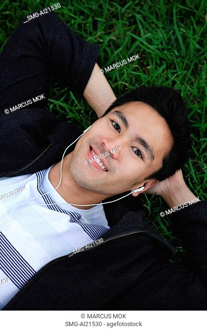 Man outdoors, listening to MP3 player, lying on grass
