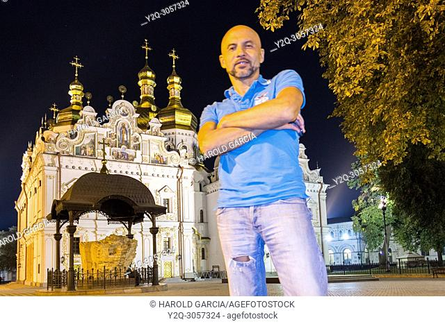 Man standing near the Orthodox cathedral Kyiv Pechersk Lavra in Kiev, Ukraine