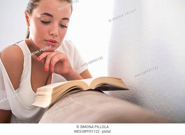 Young woman reading book on the couch
