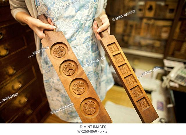 A small artisan producer of specialist treats, sweets called wagashi. A woman holding shaped wooden moulds used in the production of sweets