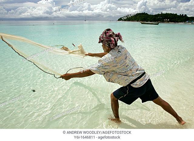 Fisherman casting net by hand Pattaya Beach Ko Lipe island Thailand