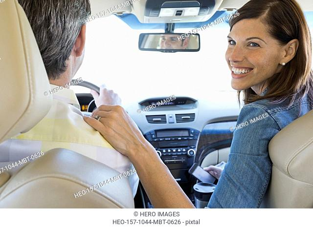 Smiling woman sitting with husband in minivan