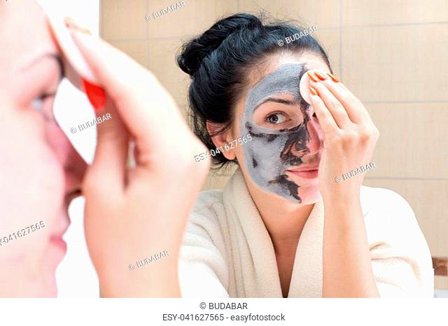 Young pretty woman in bathrobe removing facial mask in front of mirror in bathroom. Skin care and beauty concept