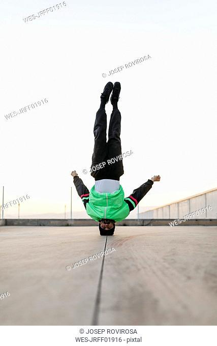 Man doing breakdance in urban concrete building, standing on head