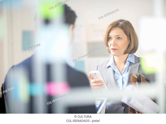 Mature businesswoman meeting with smartphone and blueprints in office