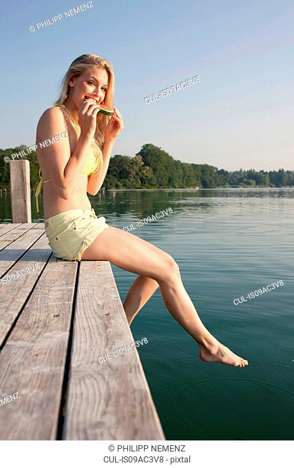 Portrait of young woman on pier eating watermelon