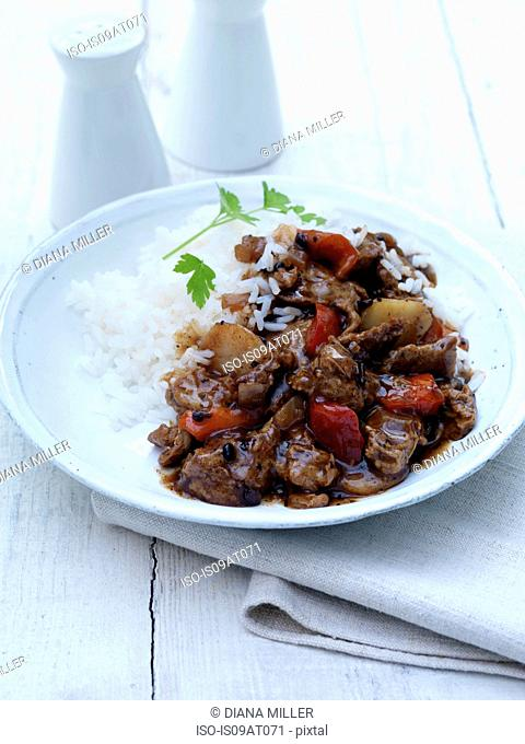 Still life of black bean sauce stir fry with potatoes and red peppers and rice on white plate
