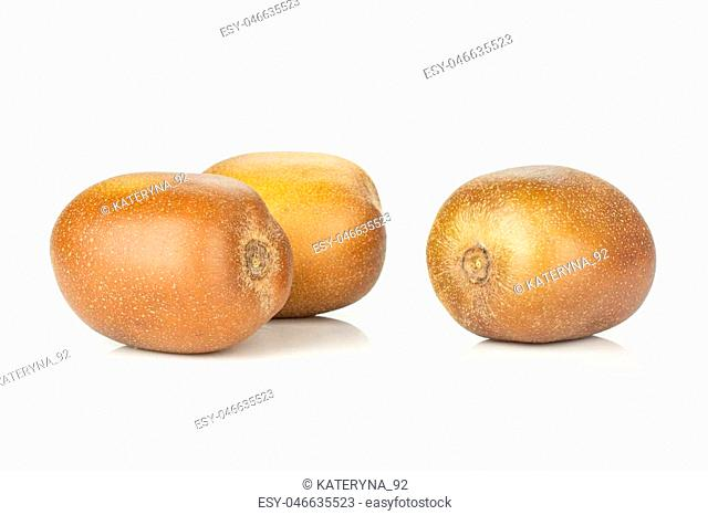 Group of three whole fresh golden brown kiwi fruit sungold variety isolated on white