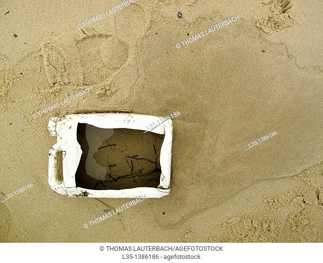 Cut-open plastic container on the beach