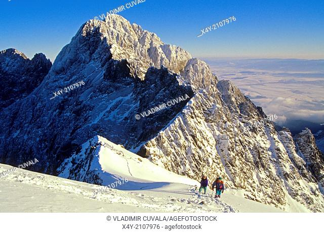 Two mountaineers on the track leading from Baranie sedlo to Baranie rohy, with the view of Pysny stit in the distance, High Tatras